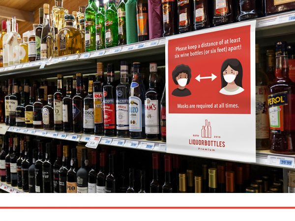 Shelves of wine bottles with a social distancing sign