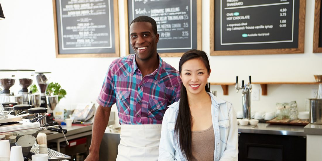 Man and woman standing in front of a menu board in a cafe